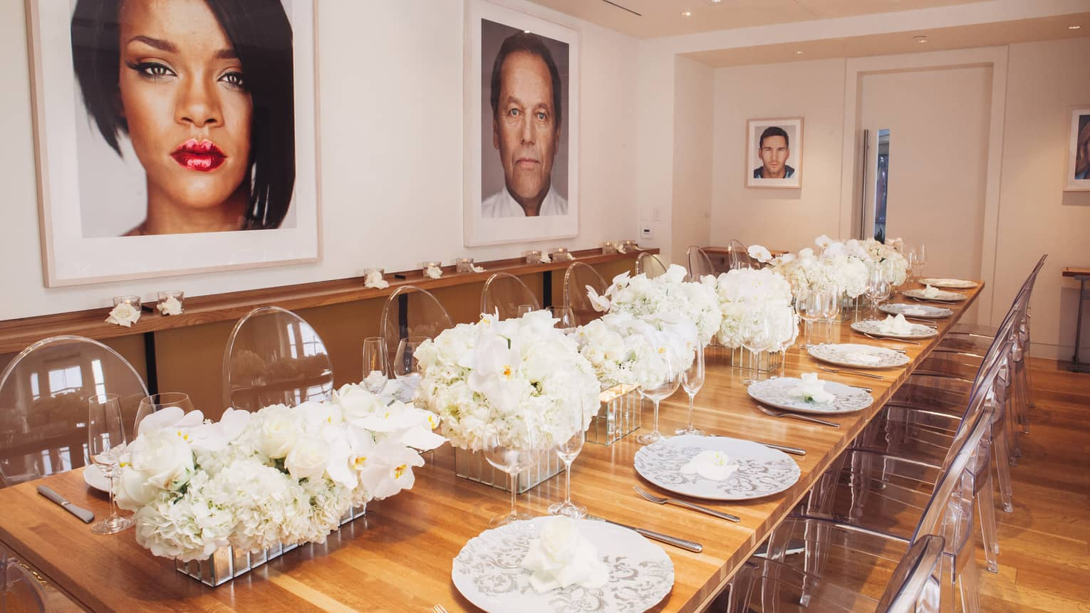 Petit Cut long wood banquet table with white roses, clear chairs, under framed prints of Hollywood stars