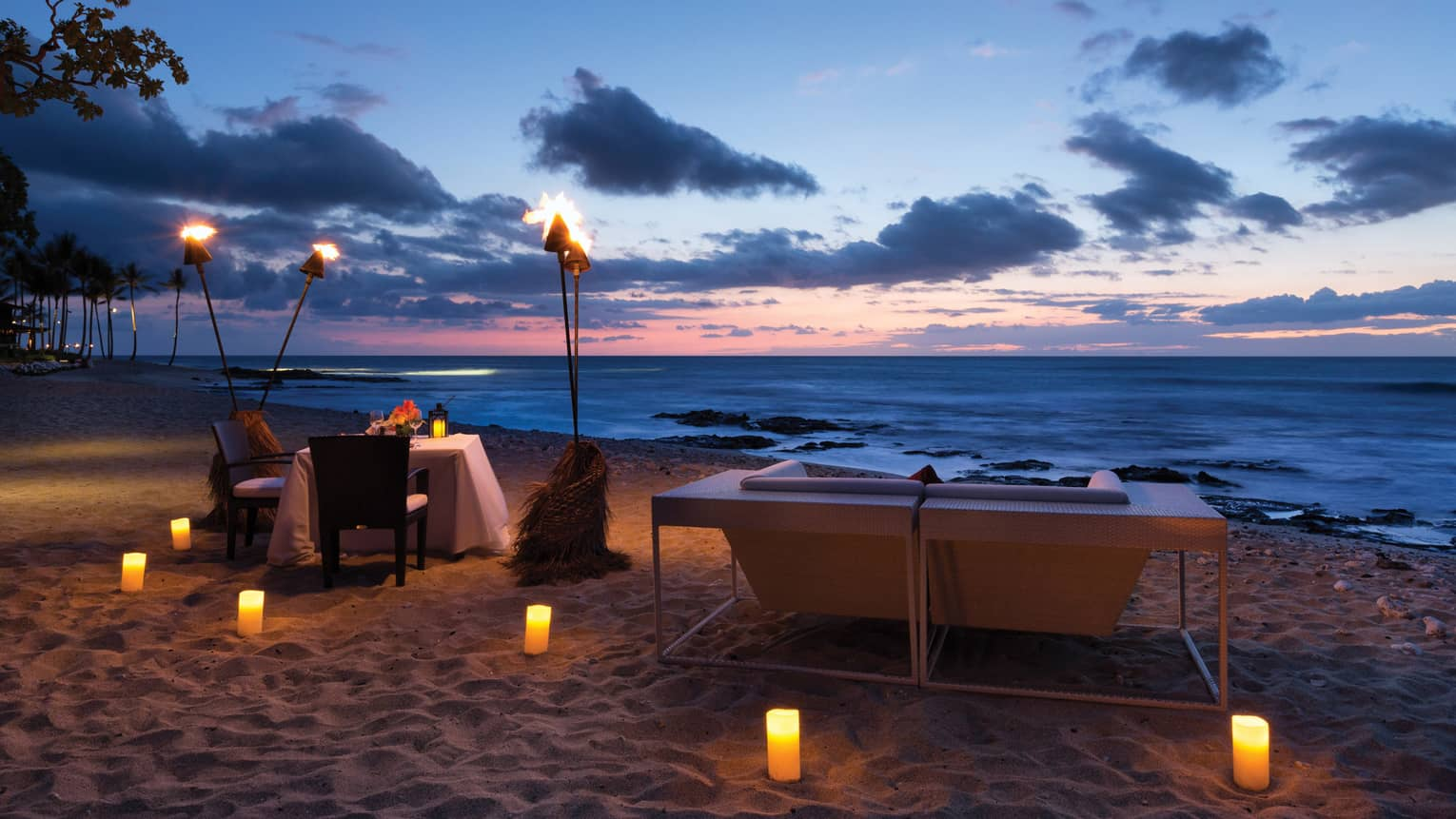 Torches Over Dining Table On Beach At Night Glowing Candles In The Sand