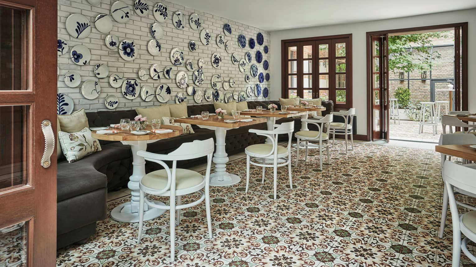 Blue-and-white decorative plates on wall over velvet banquette, cafe tables and chairs, tile floor