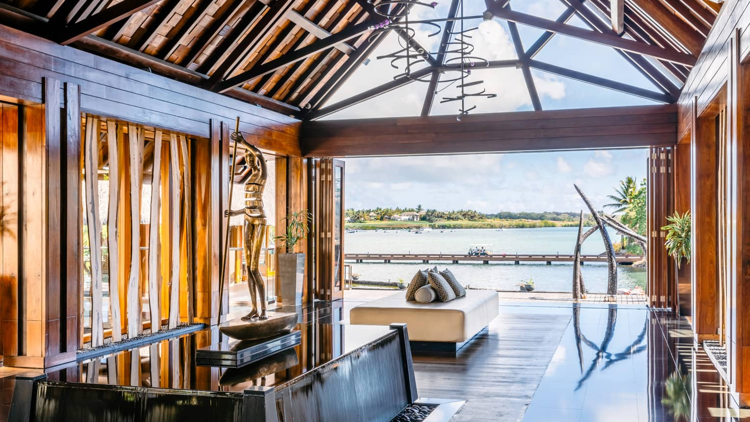 Resort lobby with vaulted wood ceiling and view over barachois and Indian Ocean lagoon