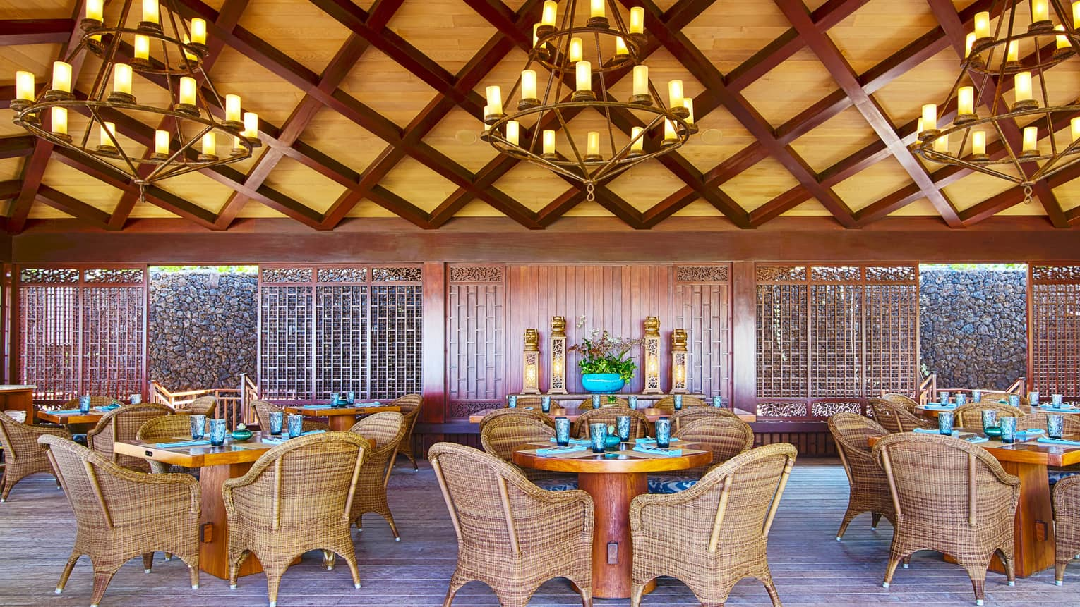 Dining area under bamboo and lattice ceiling with three chandeliers, round dining tables and wicker chairs