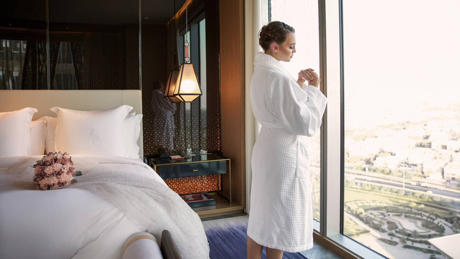 Woman wearing white bathrobe, braids in hair gazes out hotel room window, wedding bouquet on bed