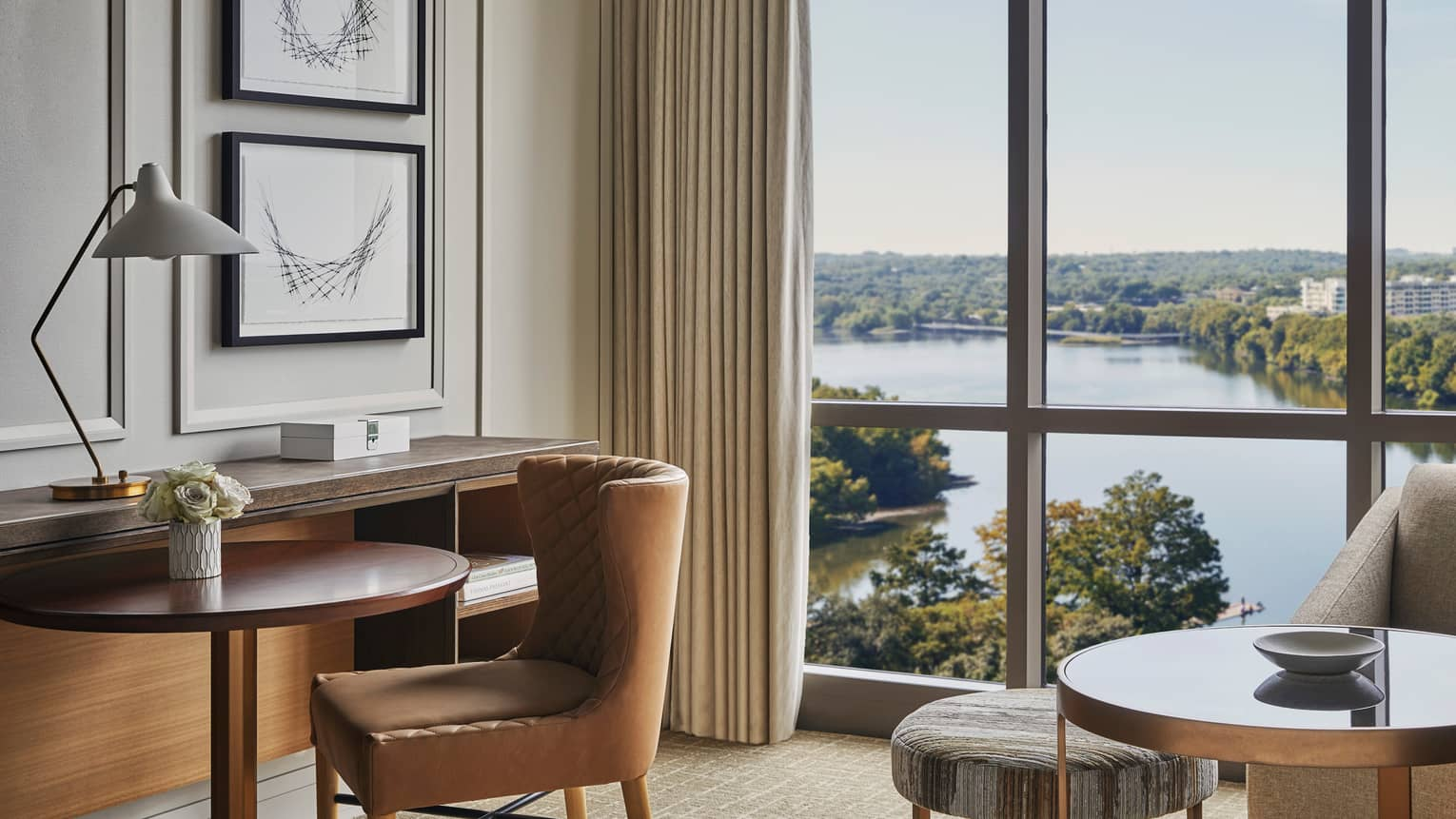 Leather chair by small hotel dining table, floor-to-ceiling windows, Lady Bird Lake views