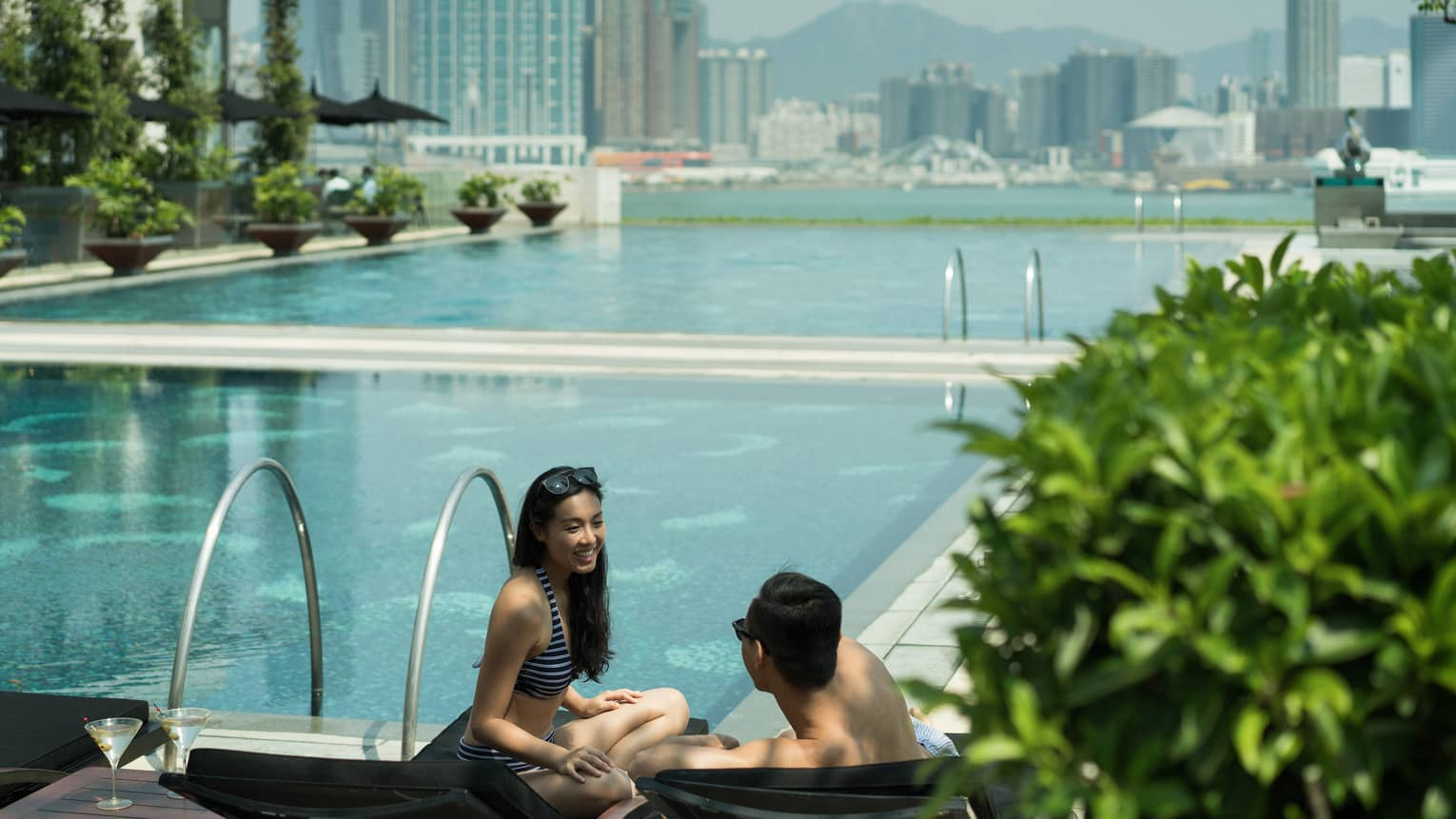 Couple wearing swimsuits on outdoor swimming pool deck, city skyline in background