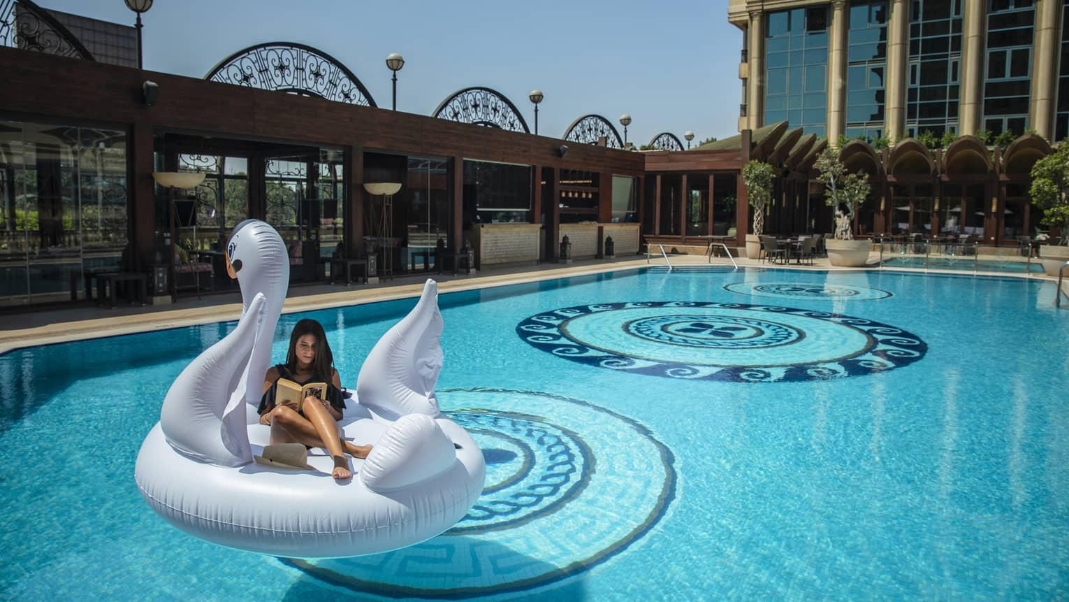 A woman reads a book while floating on a large inflatable swan at the book