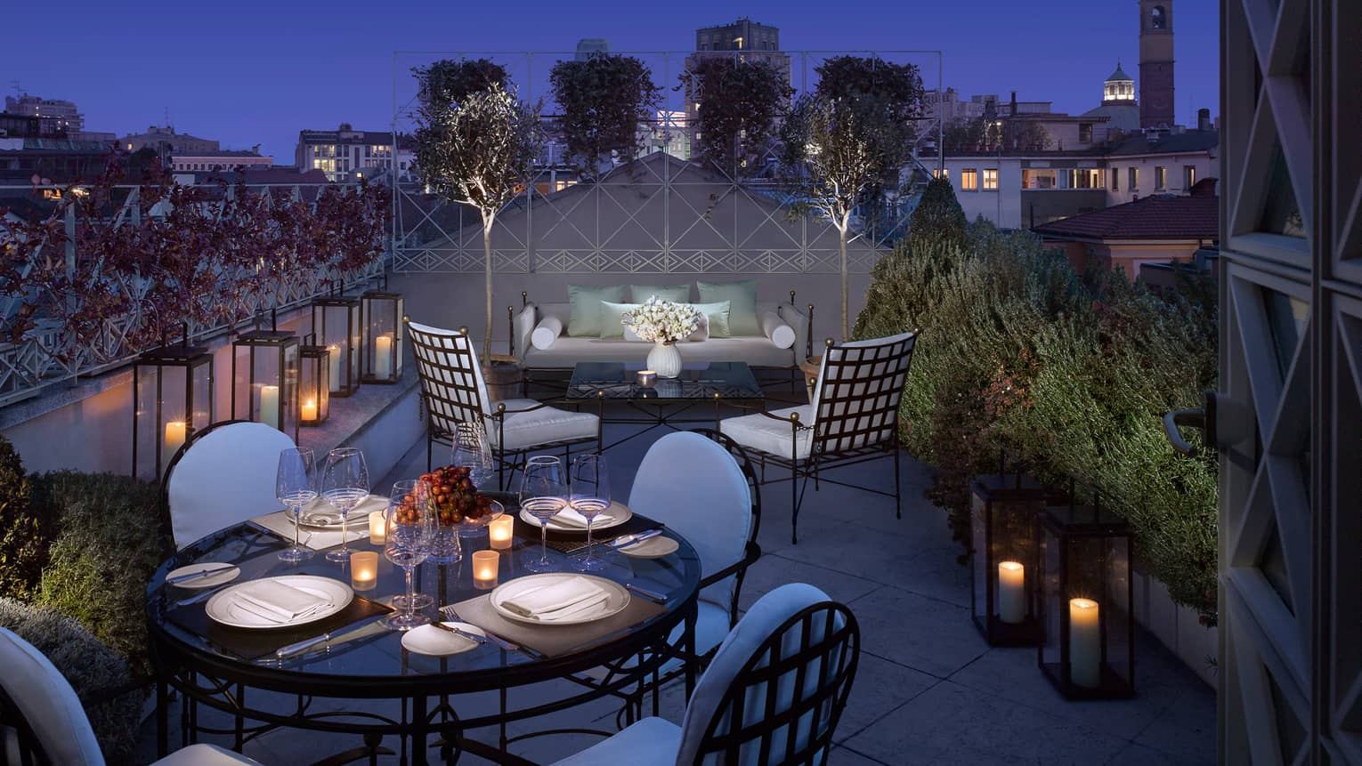 Penthouse Suite lantern-lined rooftop balcony, candle-lit dining table, patio sofa and chairs at night