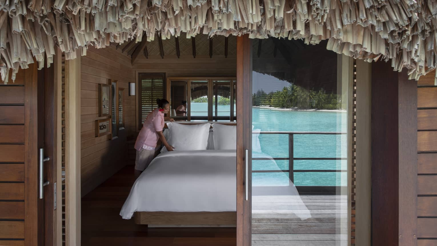 View through overwater bungalow sliding glass door to hotel bed