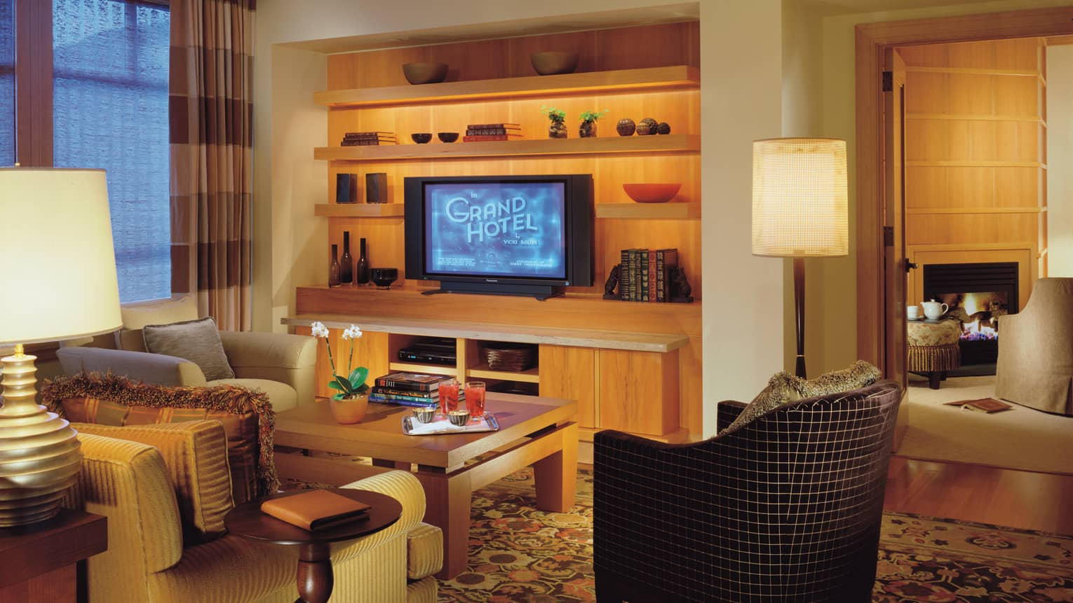 Two-Bedroom Panorama Suite living room with TV displaying Grand Hotel on shelf with art