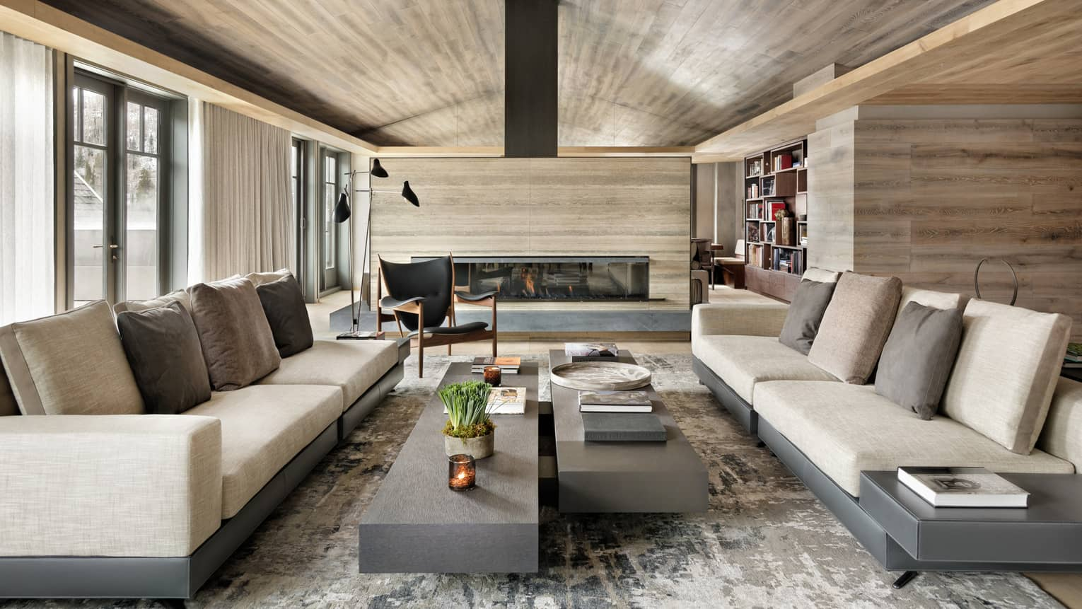 Long linen sofas, slate coffee tables under modern light wood ceiling, fireplace