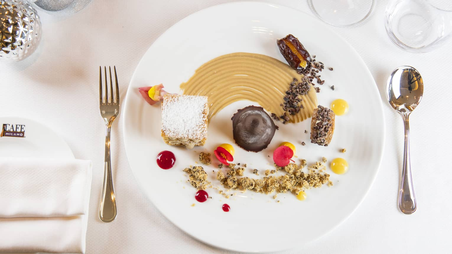 A dessert plate with various decadent mini desserts on it, on a clean white plate and white table cloth
