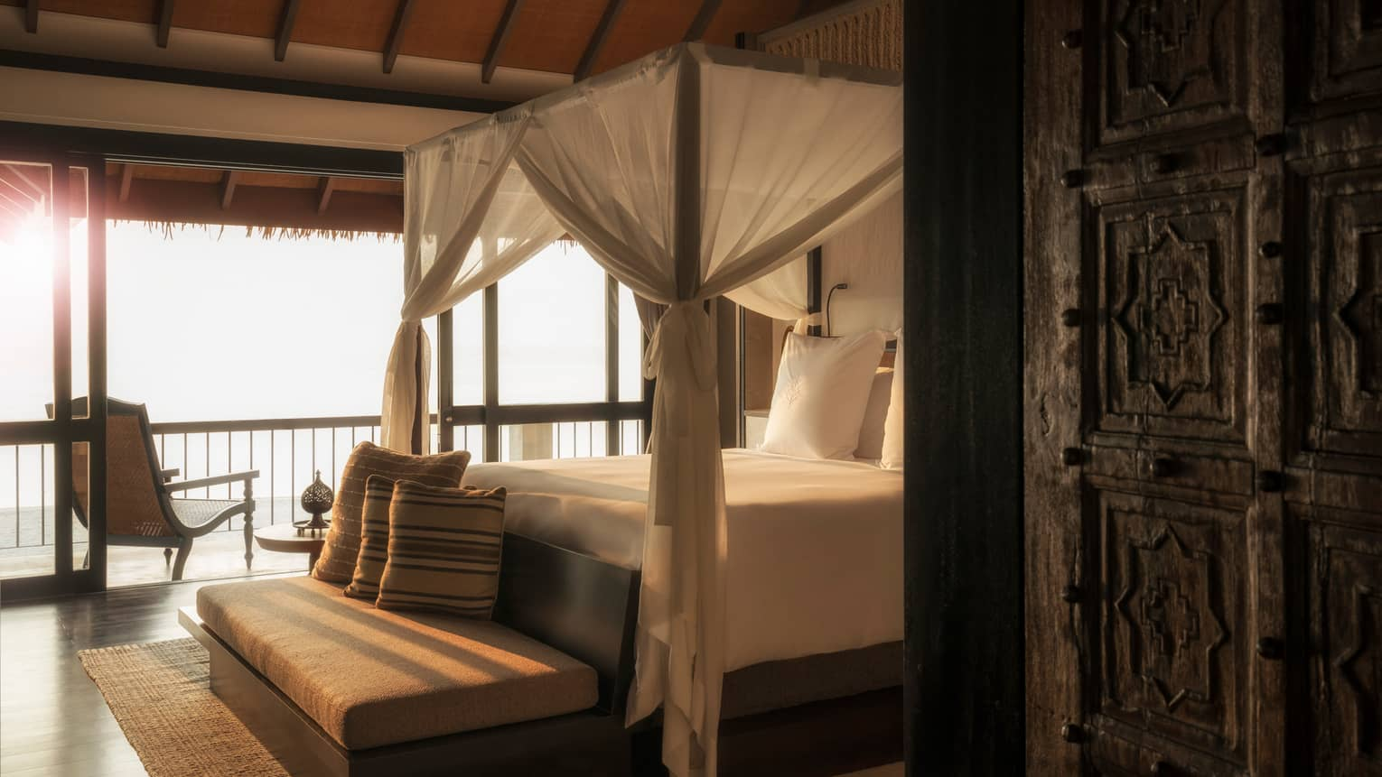 Mezzanine Suites cushioned bench with pillow at foot of canopy bed with white curtains in sunlight
