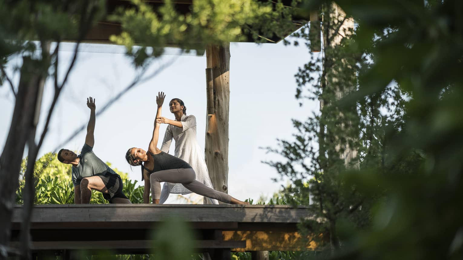 Couple stretching during outdoor yoga class