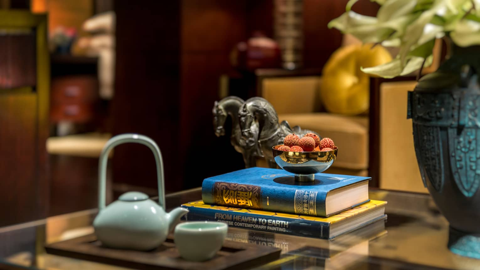 Close-up of white teapot, cup, stack of books, bowl of fruit, horse statues