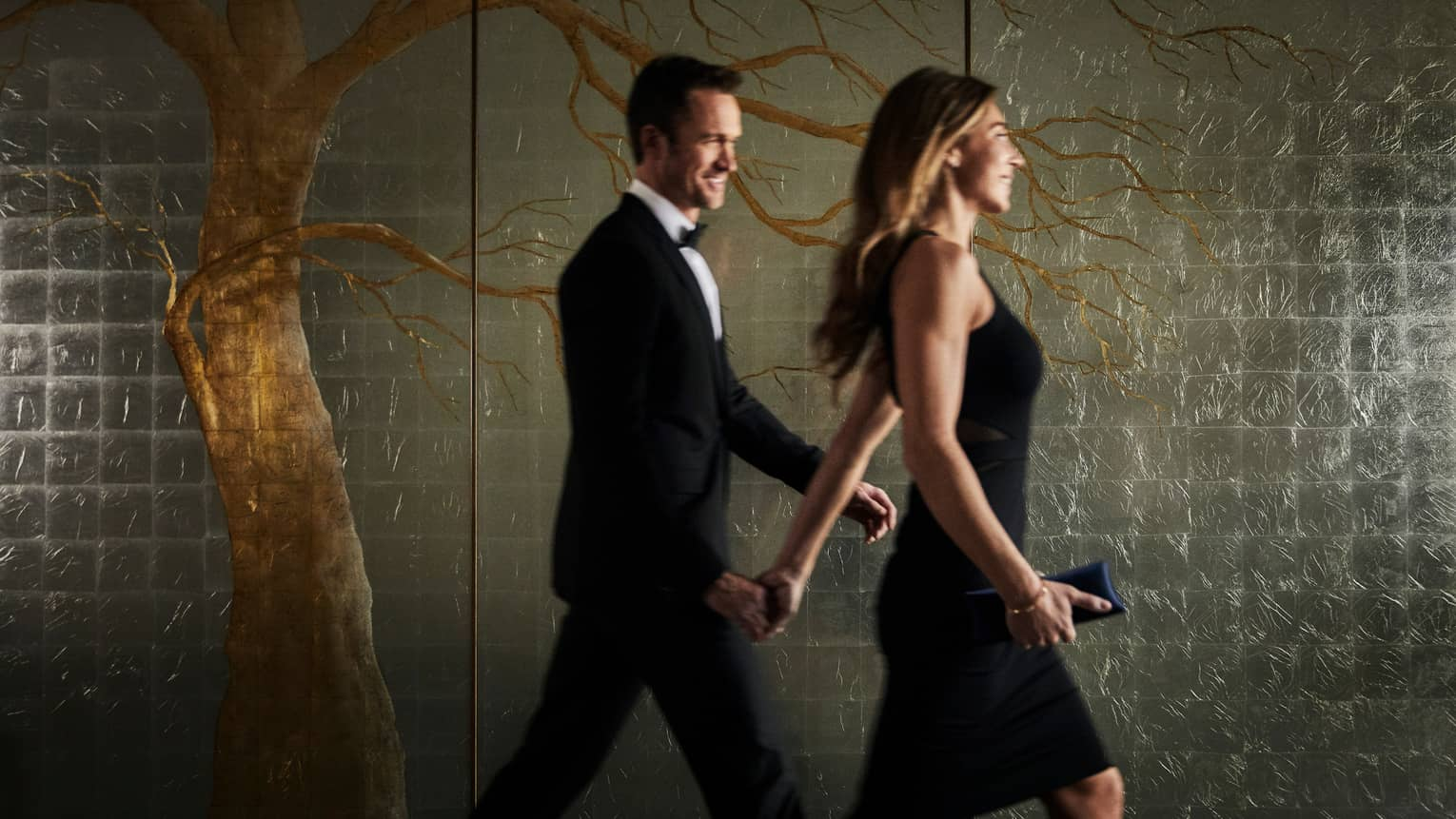 Man in tuxedo, woman in black dress walk past dark, frosted glass wall with tree mural