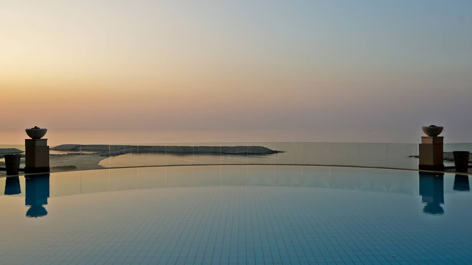 Calm and empty circular infinity pool overlooking Mediterranean Sea at sunset