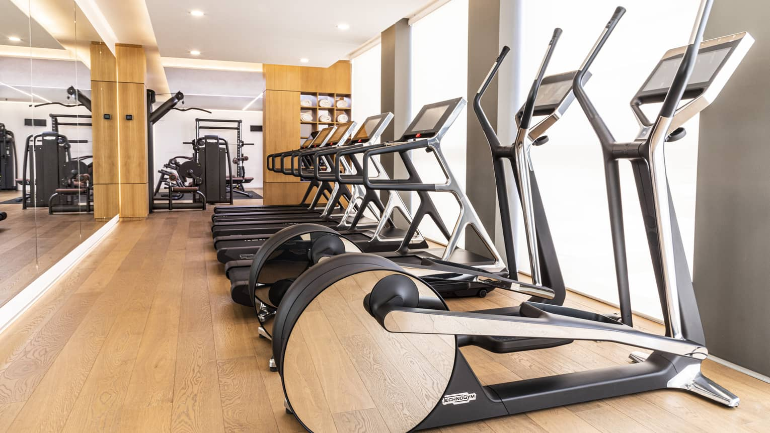 Indoor gym with a row of treadmills and elliptical machines facing windows
