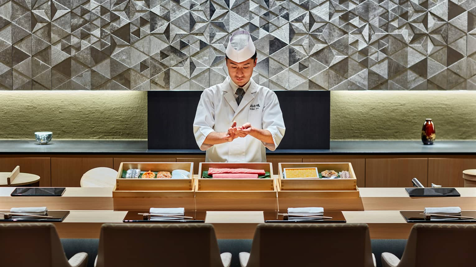 Sushi chef prepares fish behind bamboo display, Sushi wakon bar