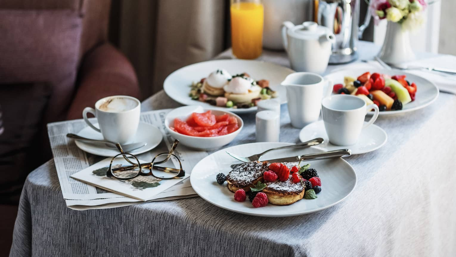 Breakfast dishes on white round dishes, square white table, orange juice, coffee, eyeglasses