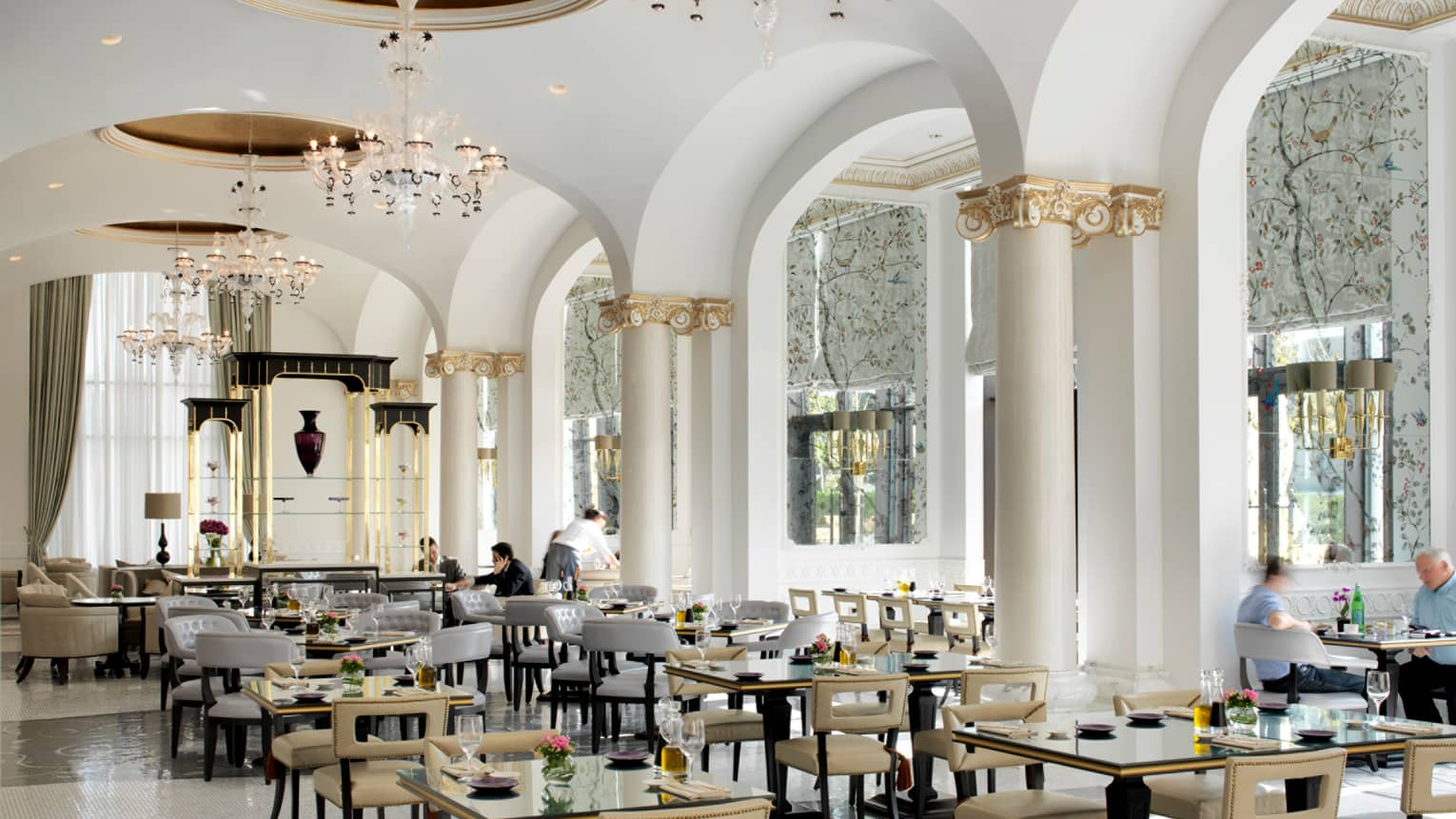 Bright Zafferano dining room with tall sweeping white ceiling, white pillars with decorative gold trim, tables and chairs below