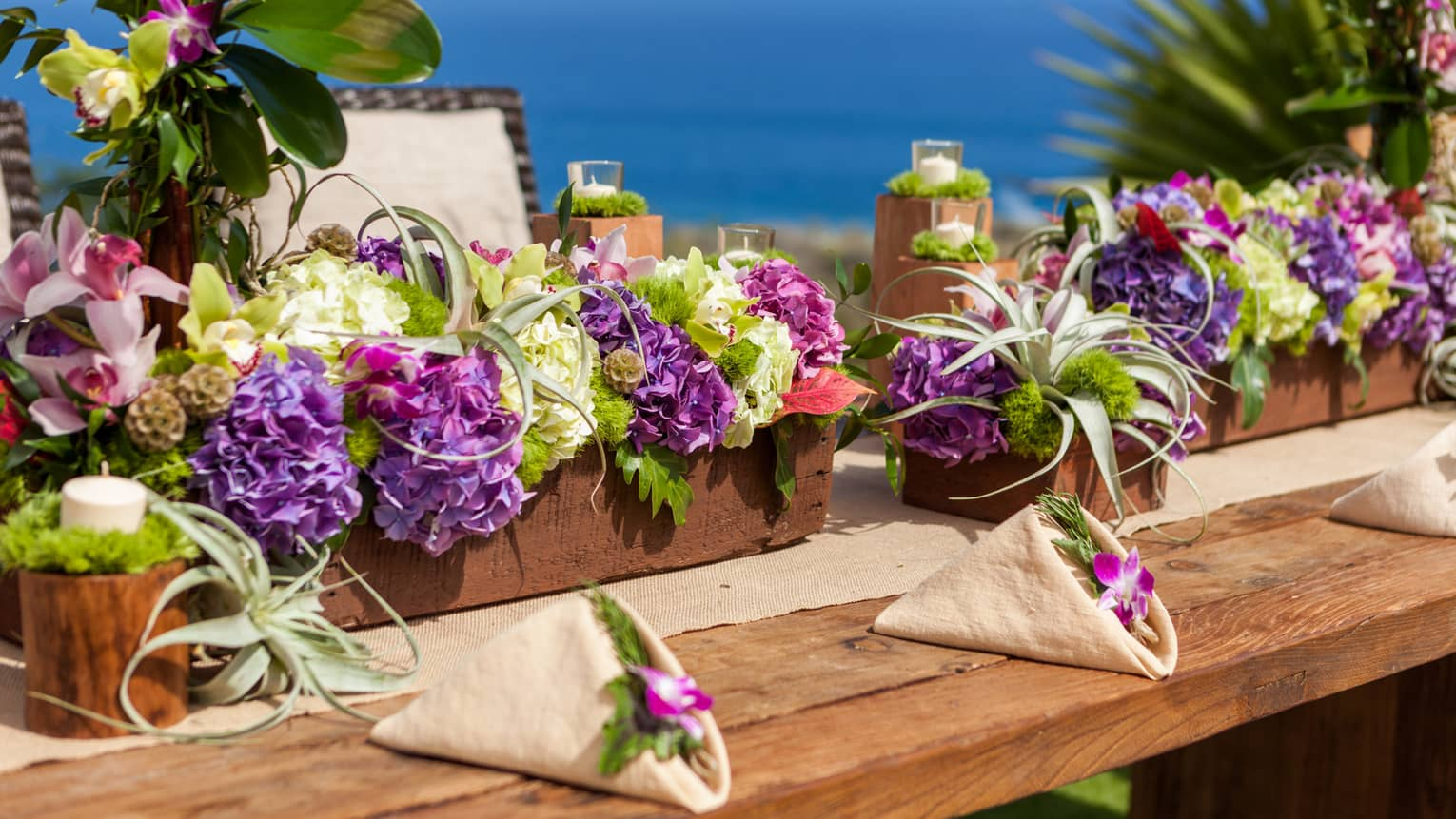 Long floral wedding centerpieces are set on a table overlooking the ocean in Lanai Hawaii