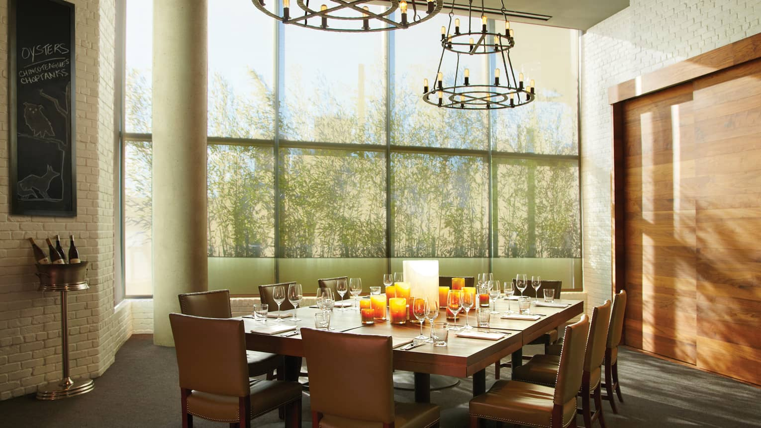 Large private dining table under modern chandelier under high ceiling, tall sunny window