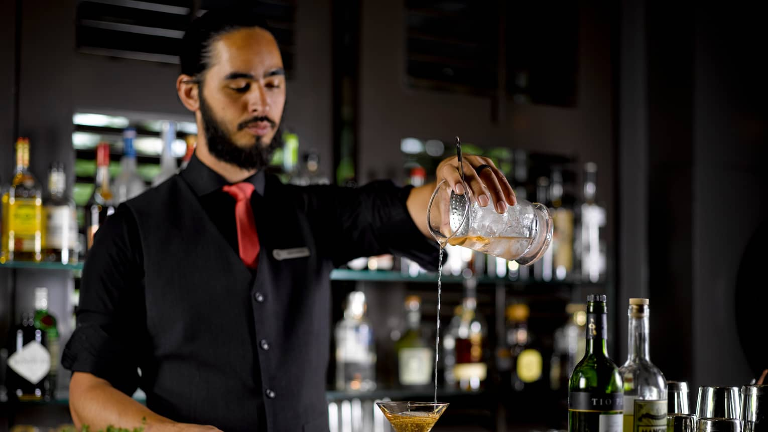 Bartender in vest, tie pours cocktail from shaker into martini glass at bar