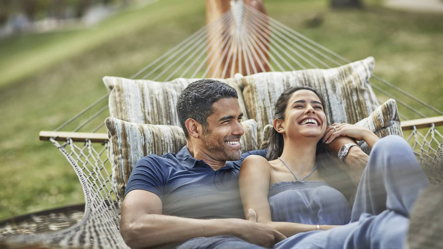 Smiling couple relaxes in hammock on lawn