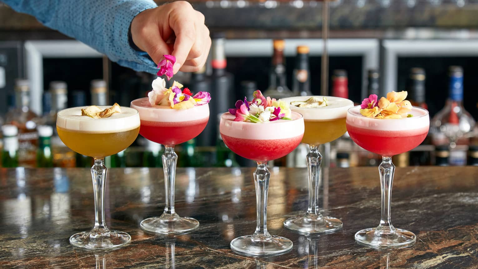 Grain bar mixologist garnishes colourful frozen cocktails with fresh flower petals