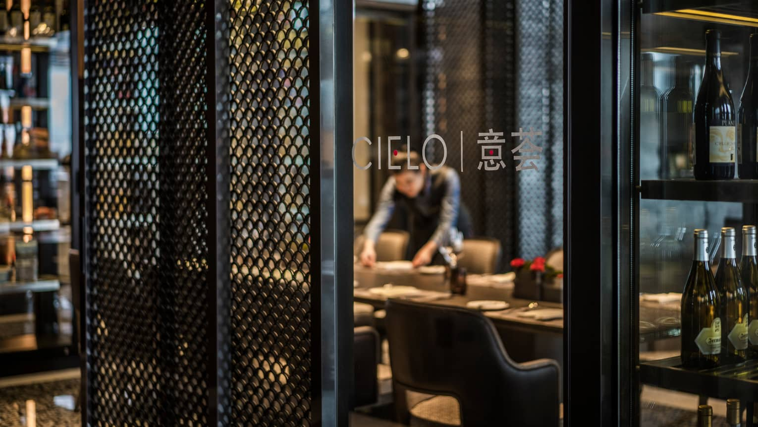 Server sets dining table behind glass wall with Cielo name, logo