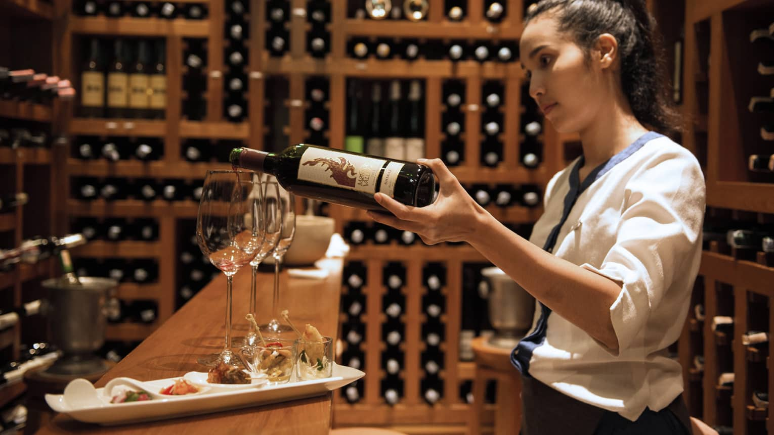 Sommelier at Koh Bar, pouring Thai wine for a guest