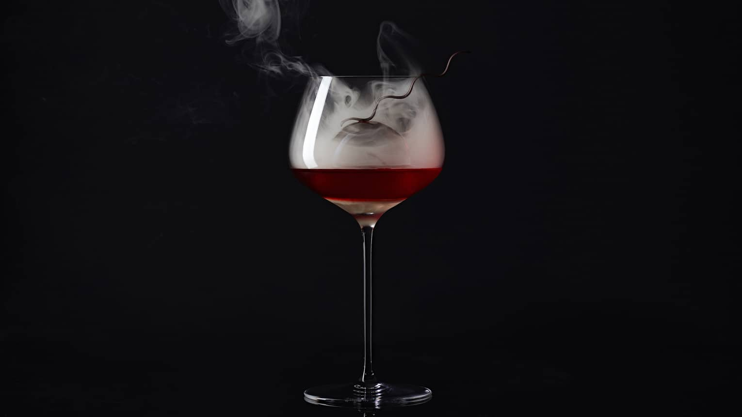 Smokey Old-Fashioned cocktail, smoke rising from tall wine glass