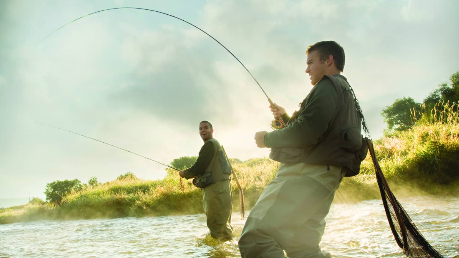 Two men standing in the water, holding rods fly fishing