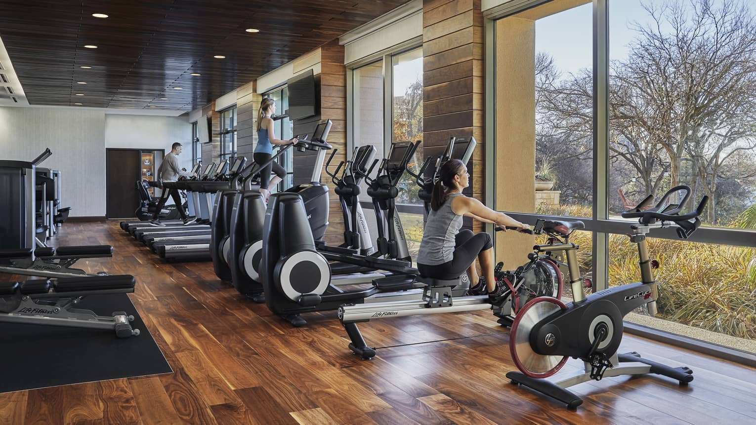 Woman sits on row machine by treadmills, cardio bikes in Fitness Centre
