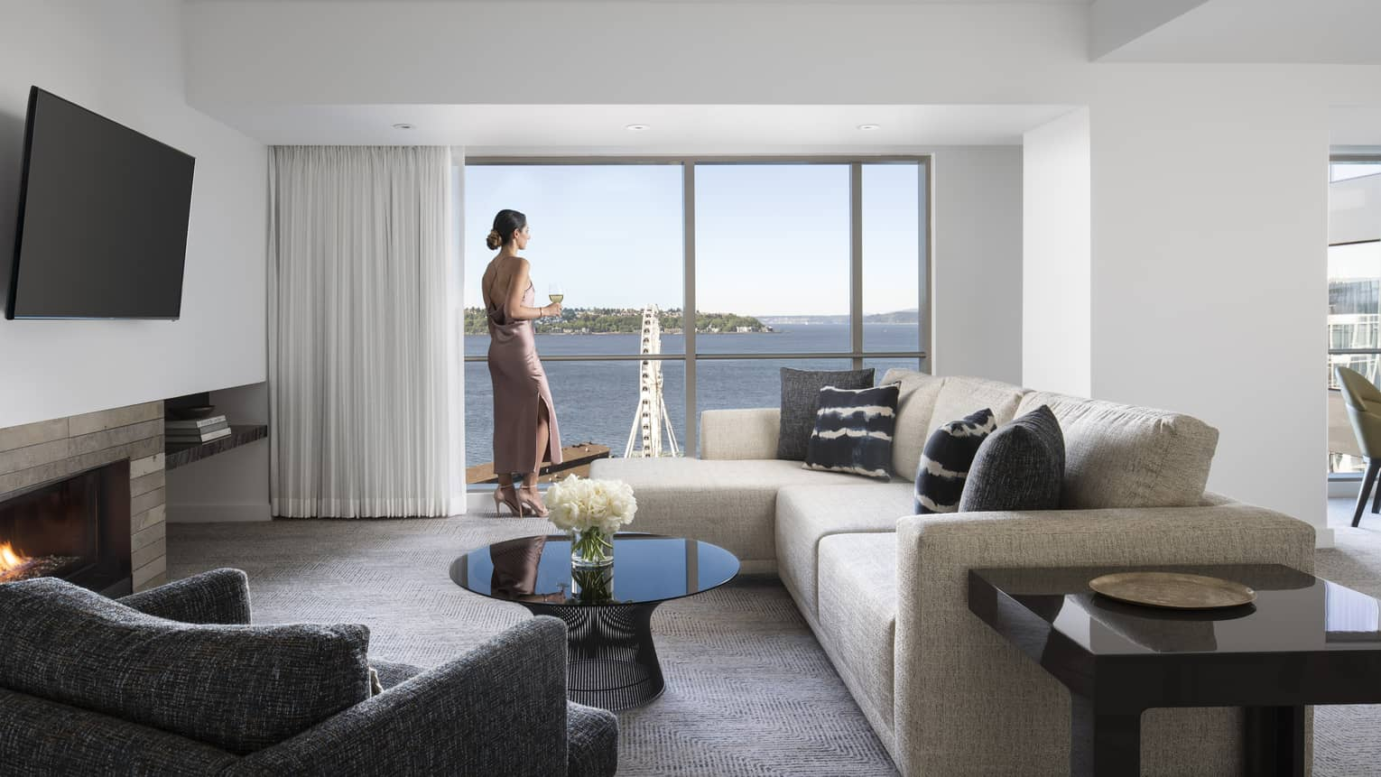 Woman stands at sunny window near L-shaped sofa in Deluxe Elliot Bay Suite