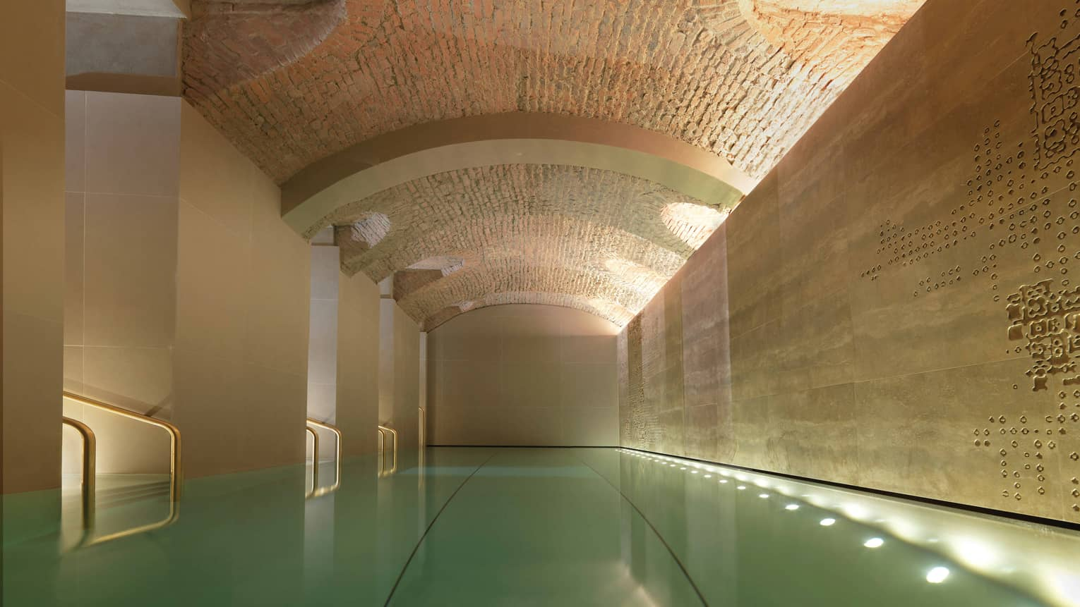 Indoor lap swimming pool with gold railings under curved stone ceiling
