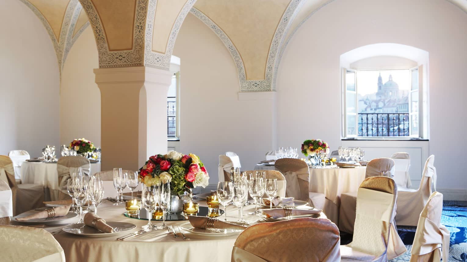 Vltava Meeting Room banquet tables under arched ceiling, sunny windows