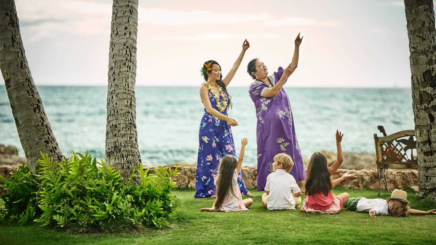 Young children sit on lawn by ocean, watch two Hawaiian women demonstrate dances