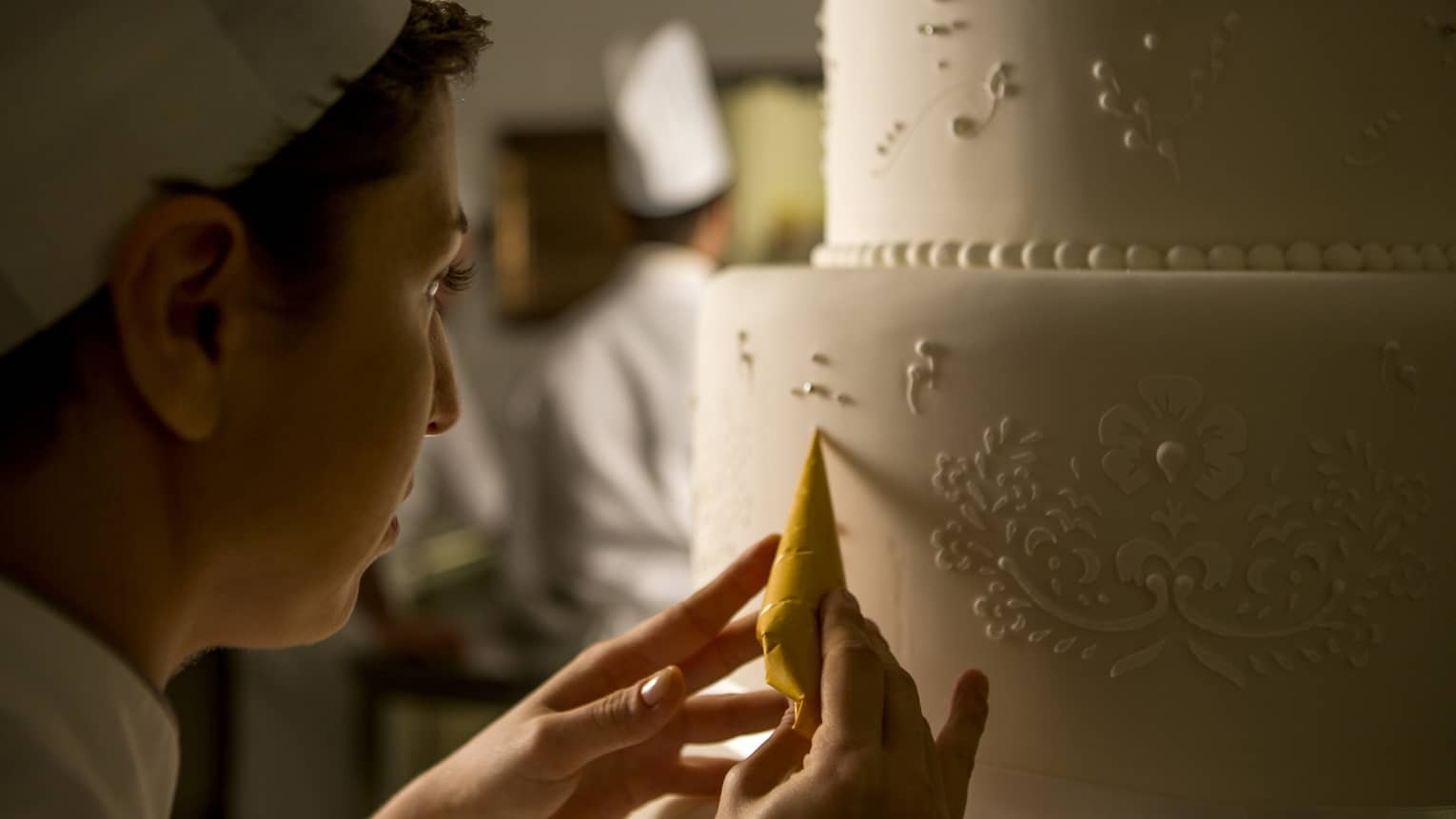 Pastry chef adds decorative details to tiered white wedding cake