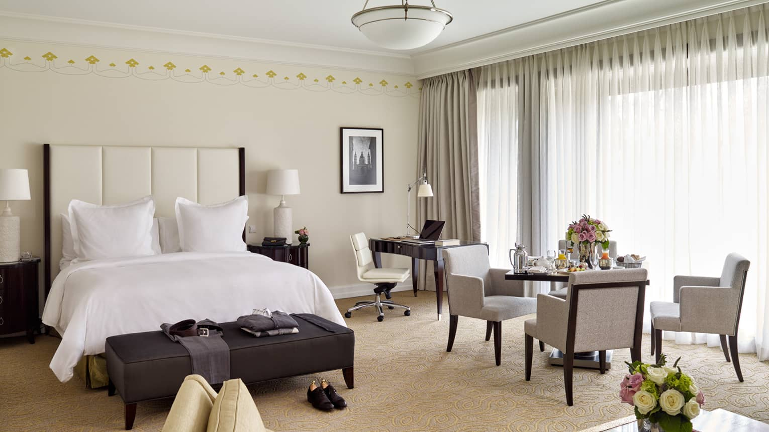 Park Suite dining table with in-room dining breakfast in front of long white curtains, beside bed and desk