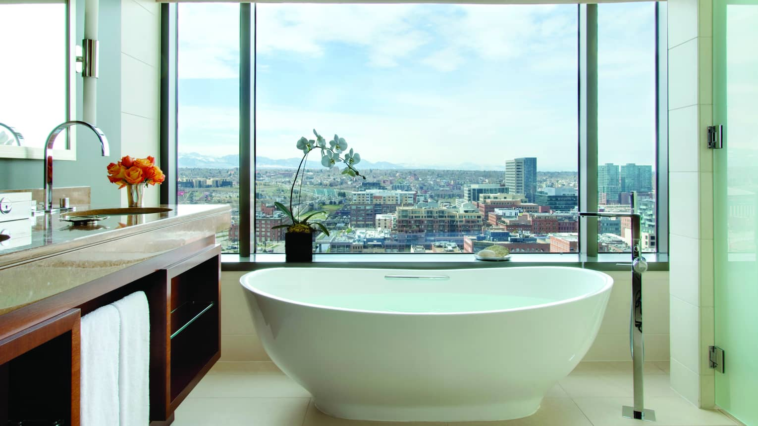 Modern white freestanding tub in marble bathroom by large window, city views