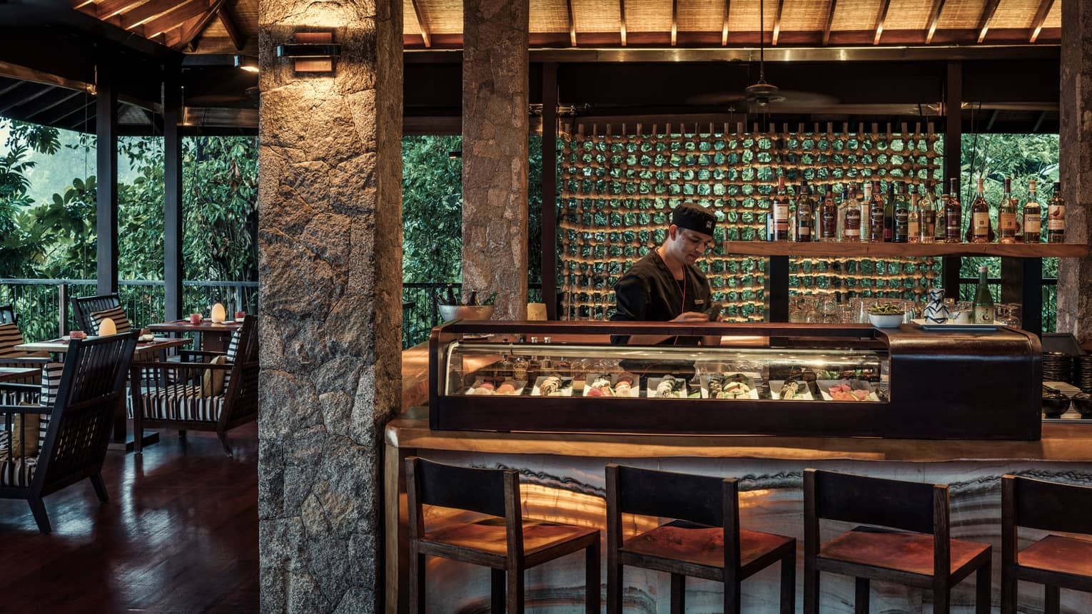 Sushi chef in black uniform stands in front of glass case in ZEZ Bar dining lounge at night