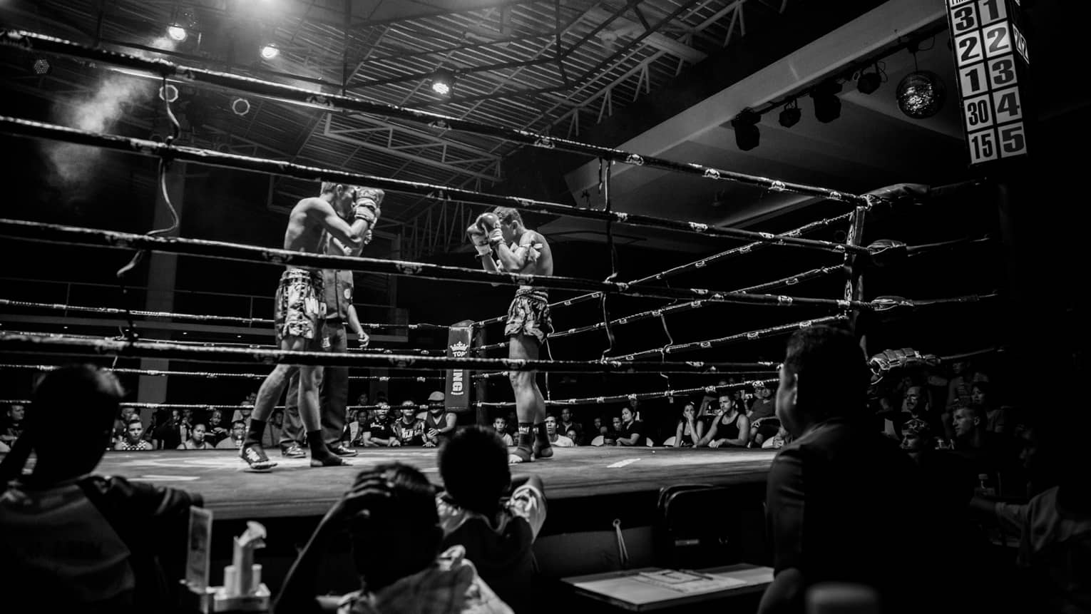 Black-and-white photo of two Muay Thai boxers in ring surrounded by spectators
