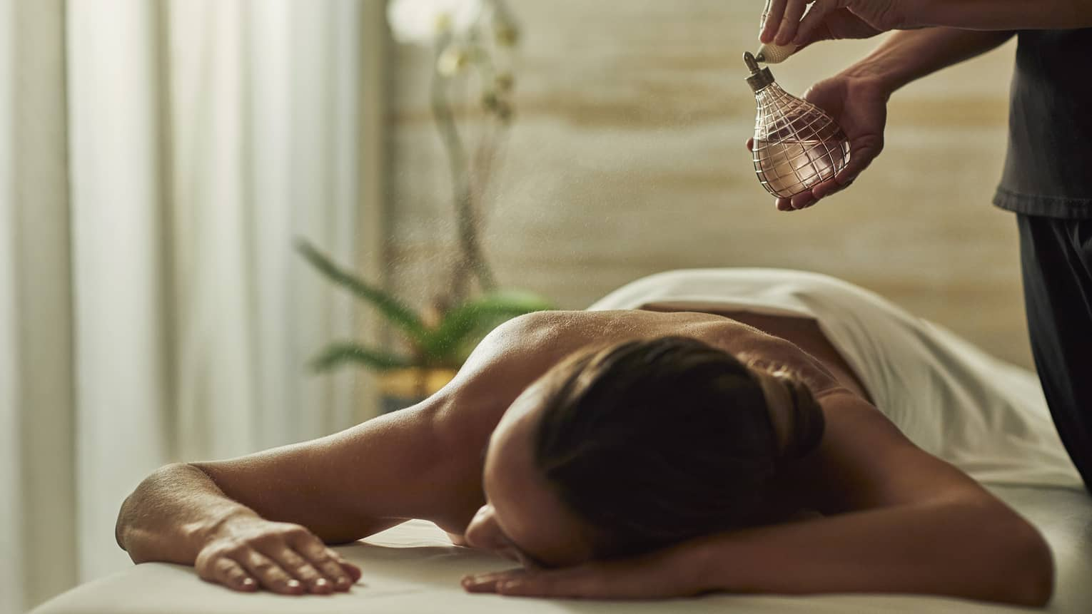 Spa staff sprays perfume bottle over woman lying on massage table