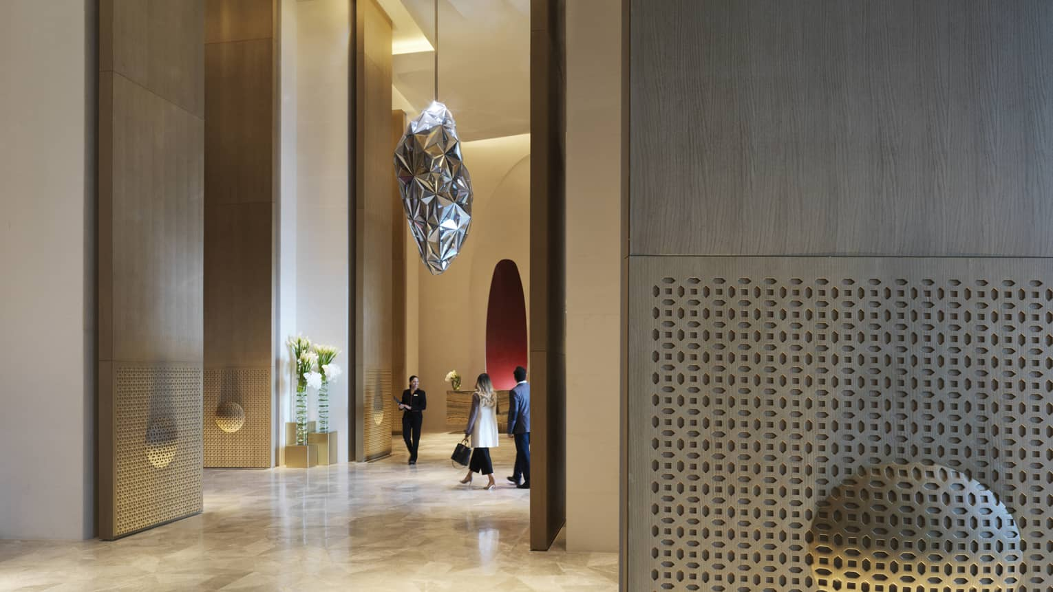 Man and woman, hotel staff walk through large modern lobby under silver sculpture hanging from soaring ceilings