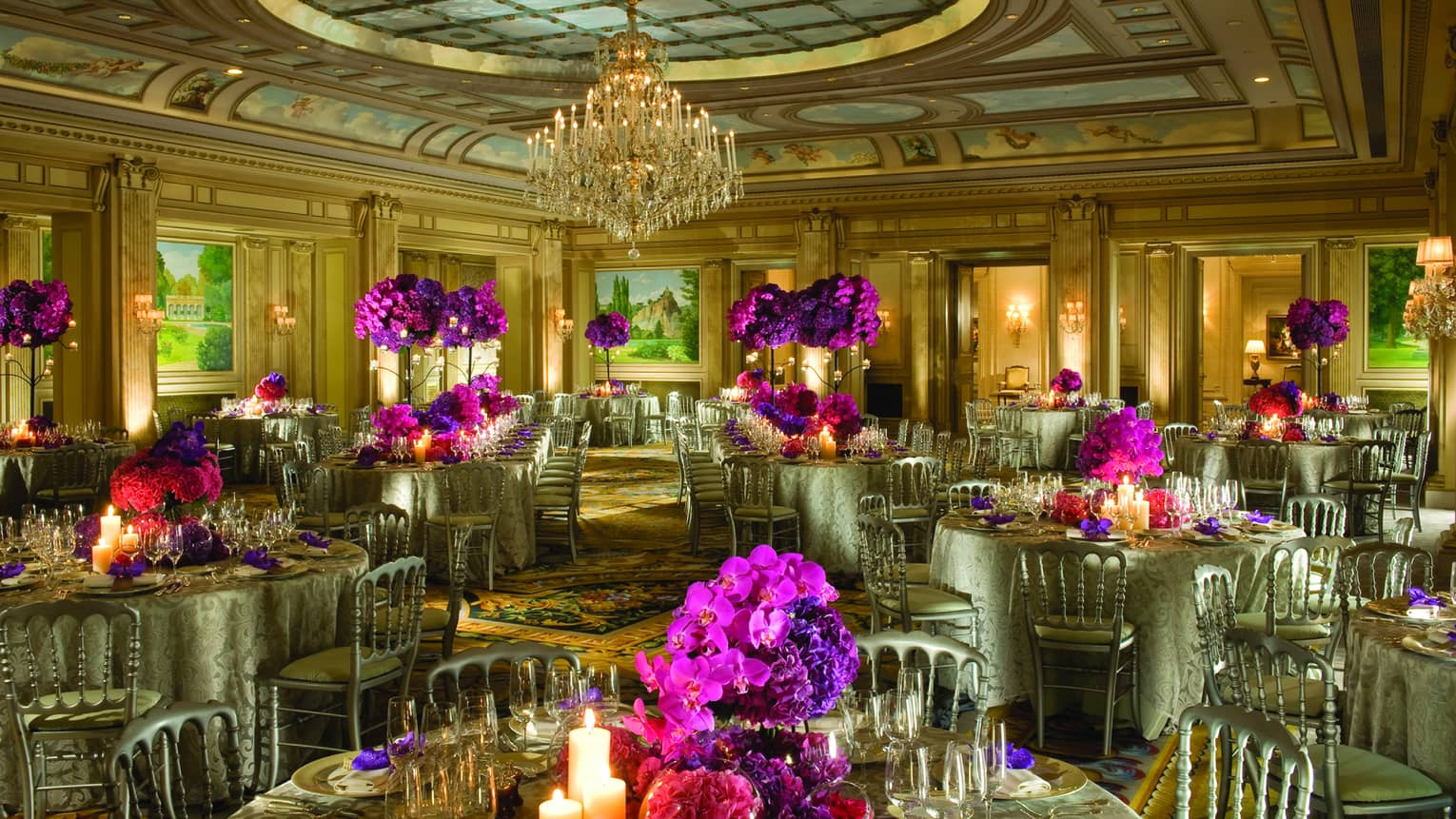 Salon Vendome round banquet dining tables with purple flowers under dome ceiling, chandelier