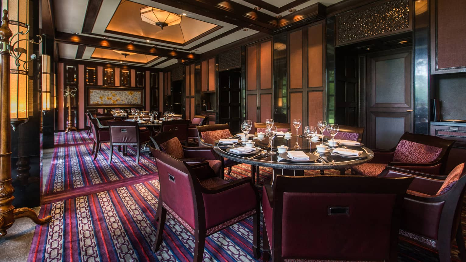 Dining tables, chairs, red-and-blue patterned rug in Jin Sha dining room