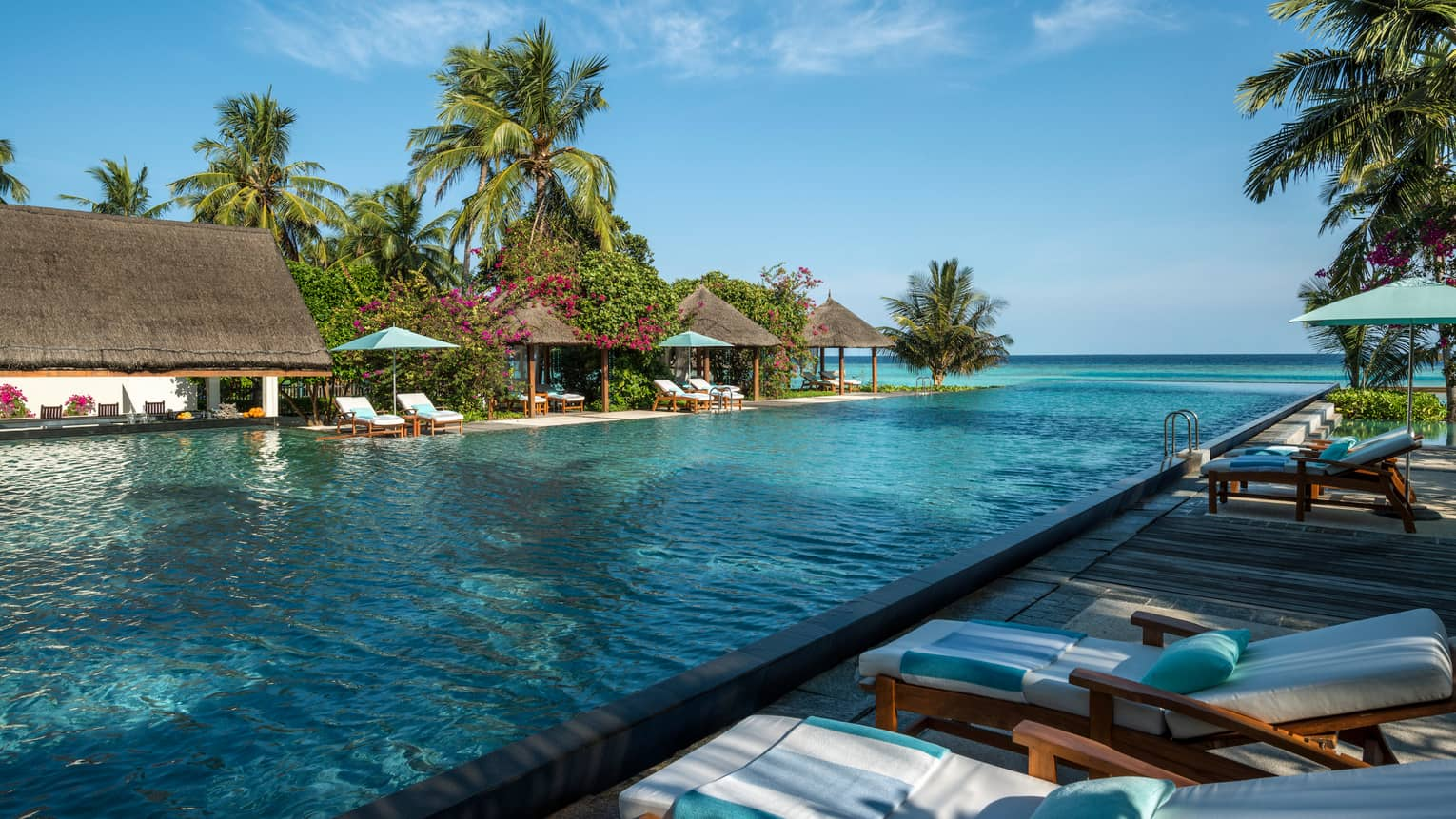 Lounge chairs, thatched roof cabanas, palm trees along outdoor swimming pool deck