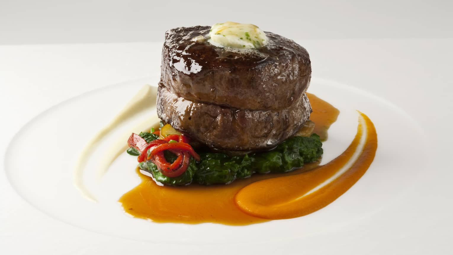 Thick Filet Mignon steak topped with melted butter, sauce on sauteed greens, peppers