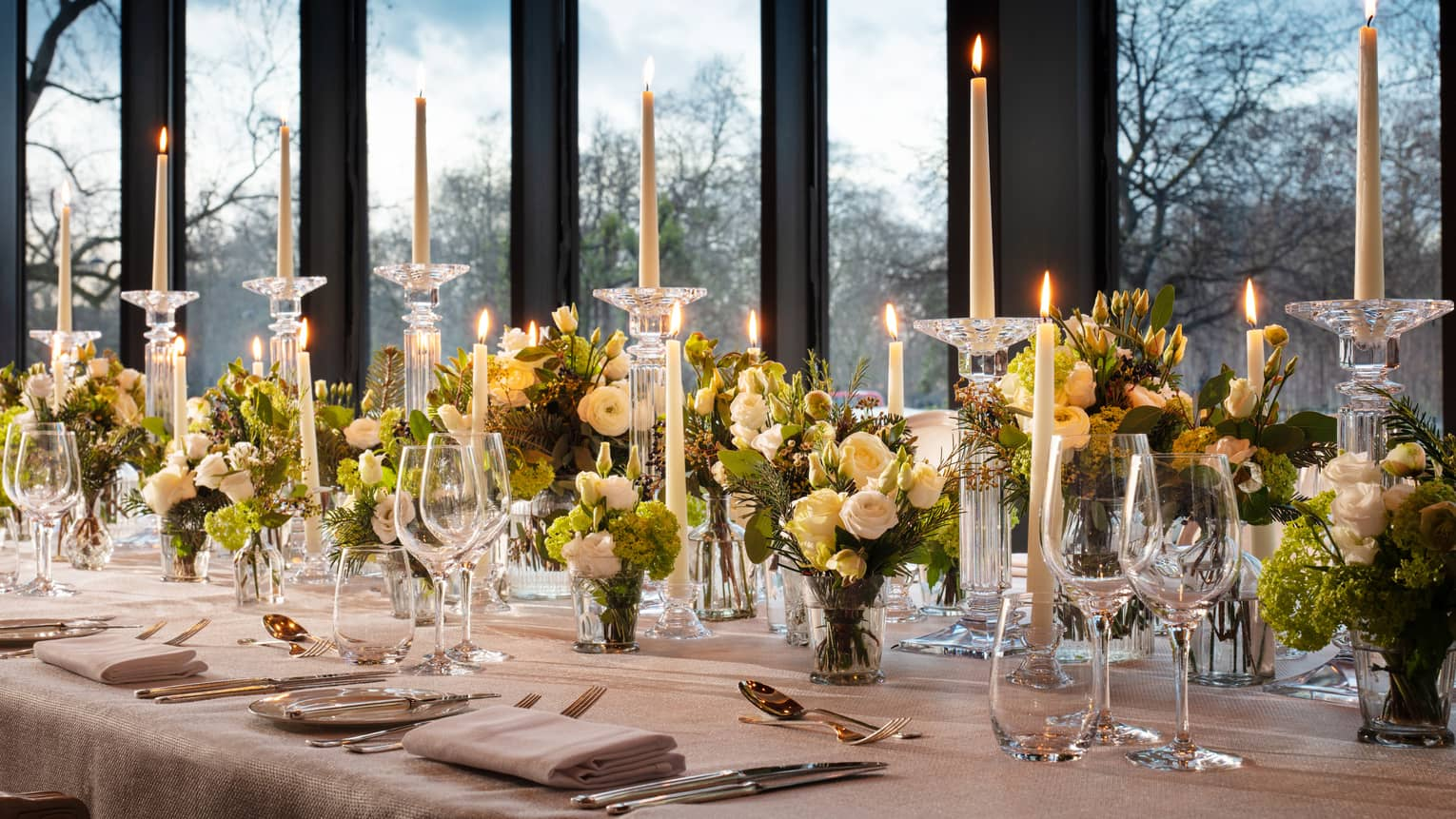 Close up shot of meeting room table set with tall tapered candles and green floral arrangements against a window backdrop