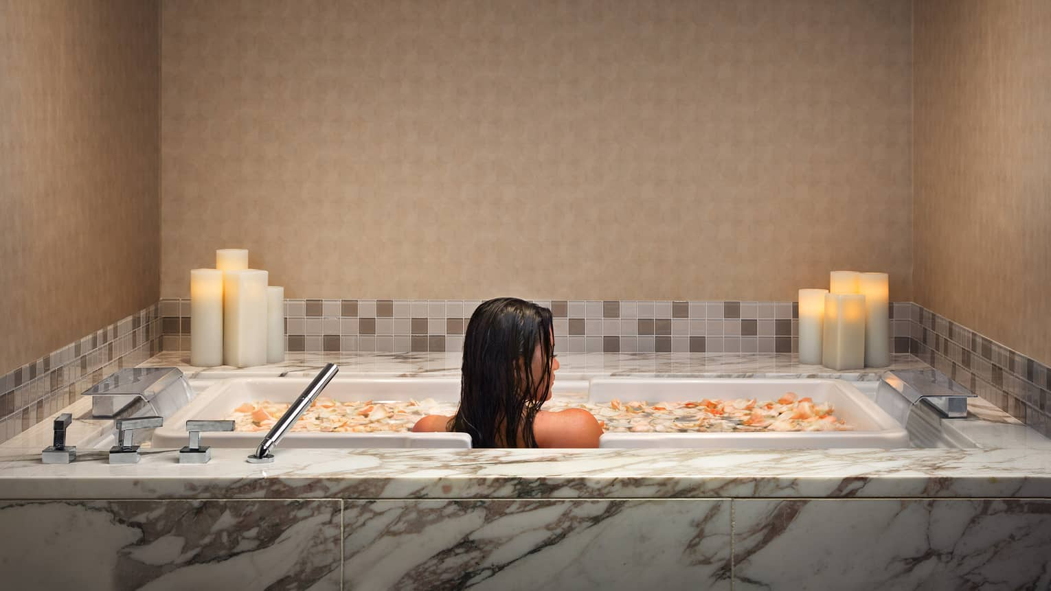 Woman soaks in marble tub filled with flower petals and lined with candles
